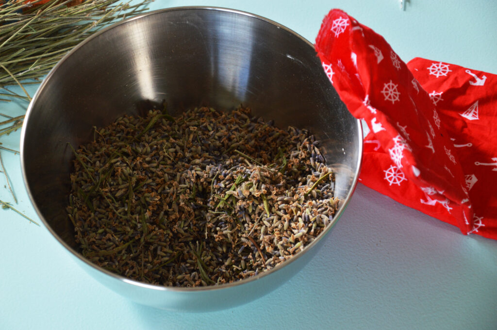 A bowl of lavender buds with a small cotton bag next to it.