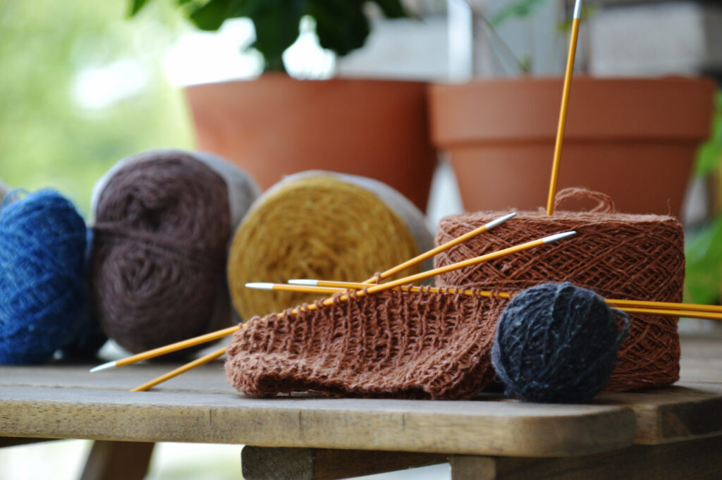 A yarn cake of terracotta coloured Holst. In the background, the contrast colours in cakes or balls and two big terracotta flower pots.