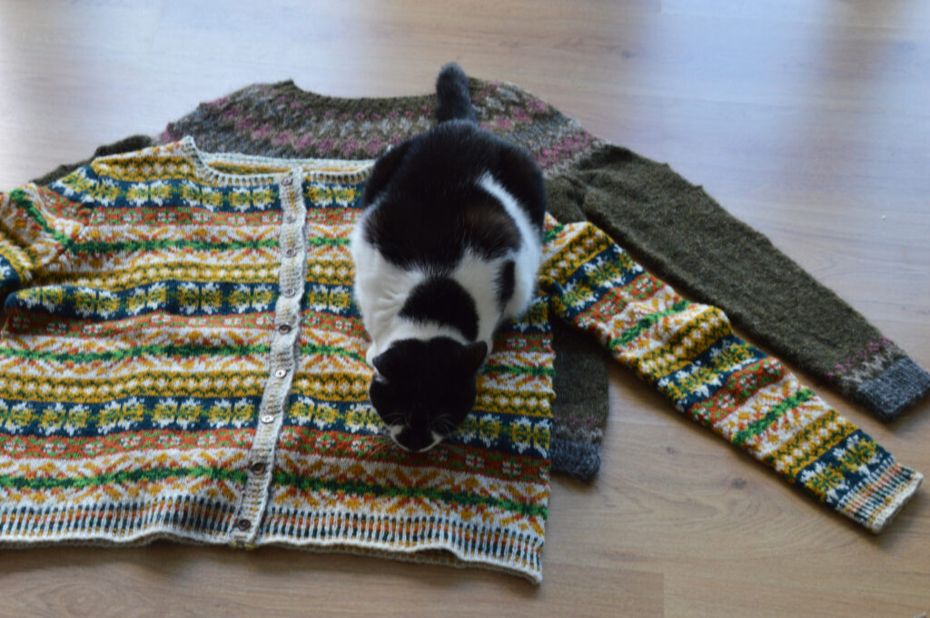A black and white spotted cat on top of two finished garments, draped over each other
